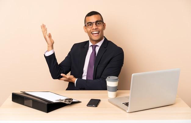 Молодой деловой человек в своем офисе с ноутбуком и другими документами, протягивая руки в сторону за приглашение прийти