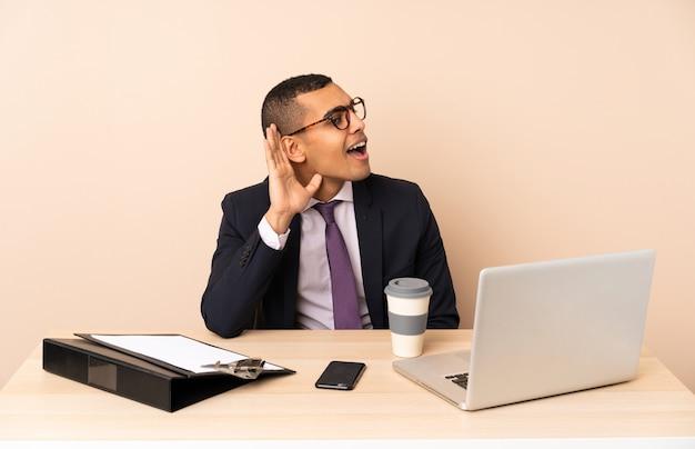 Молодой деловой человек в своем офисе с ноутбуком и другими документами, слушая что-то, положив руку на ухо