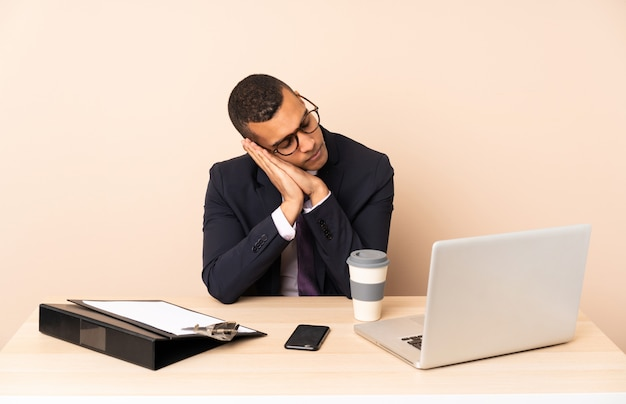 ノートパソコンと愛らしい表情で睡眠ジェスチャーを作る他のドキュメントと彼のオフィスで若いビジネスマン