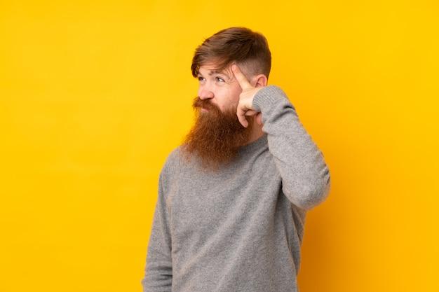 頭に指を置く狂気のジェスチャーを作る孤立した黄色の壁に長いひげを持つ赤毛の男