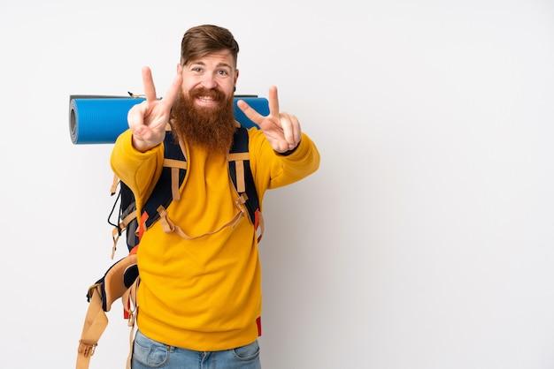 笑顔と勝利のサインを示す分離の白い壁に大きなバックパックを持つ若い登山家男