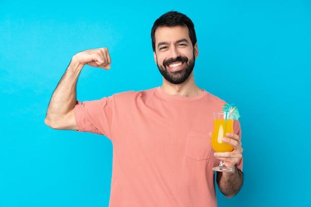 Молодой человек за коктейль над синей стеной делает сильный жест