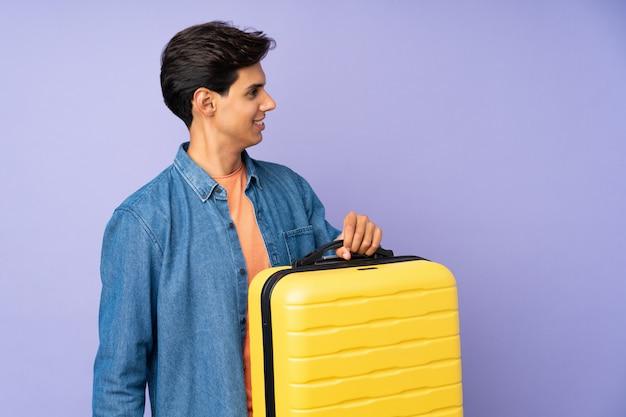 旅行スーツケースと帽子と休暇で孤立した紫色の壁の上の男