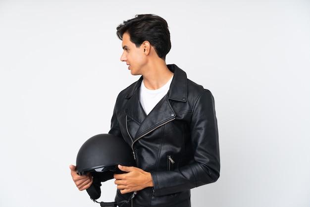 側にいる孤立した白い壁にオートバイのヘルメットをかざす男