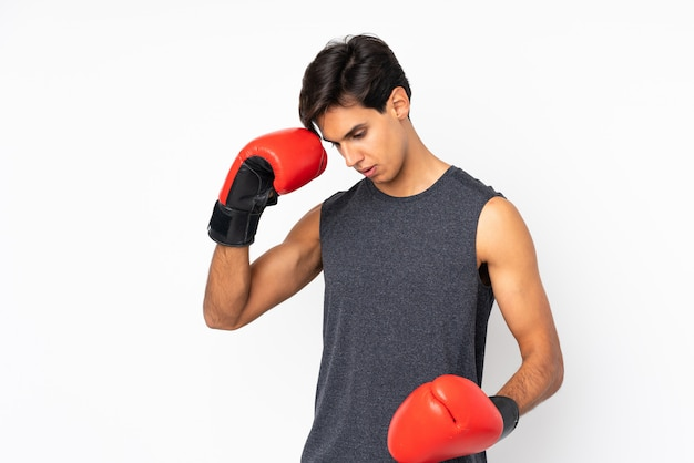 ボクシンググローブで孤立した白い壁の上のスポーツ男