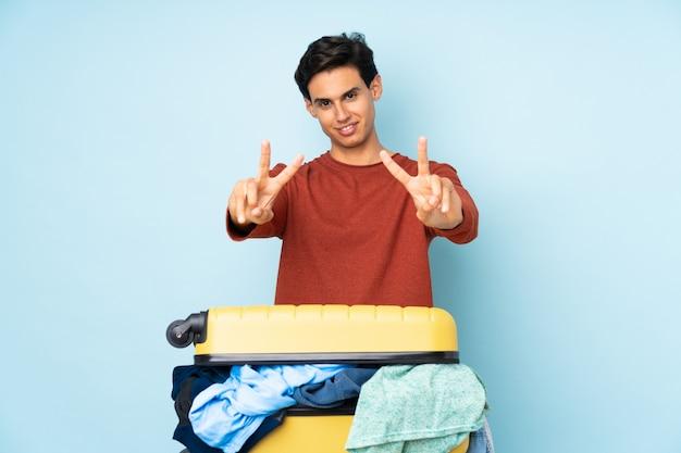 Человек с чемоданом, полным одежды над синей стеной, улыбаясь и показывая знак победы