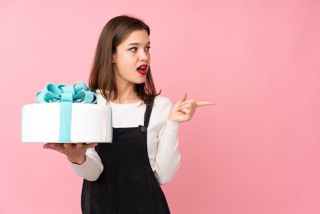 Девушка держит большой торт, изолированные на розовой стене удивлен и указывая пальцем в сторону