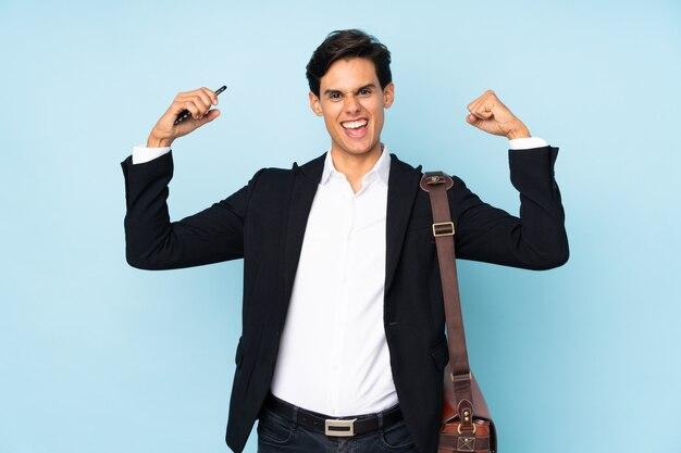 勝利を祝う分離の青い壁の上のビジネスマン