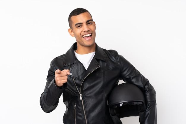 Молодой красавец с мотоциклетным шлемом над белой стене указывает пальцем на вас