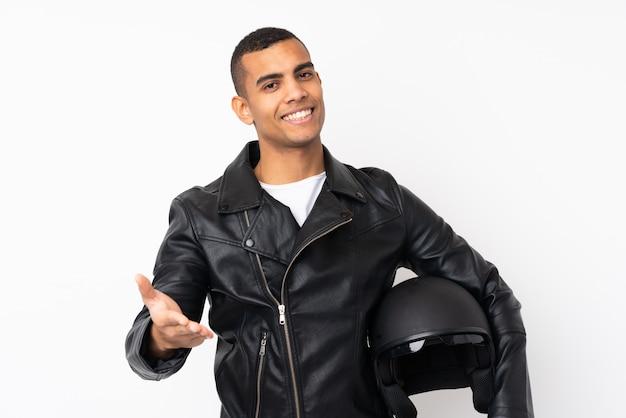 かなりの後に孤立した白い壁のハンドシェーク上のオートバイのヘルメットを持つ若いハンサムな男
