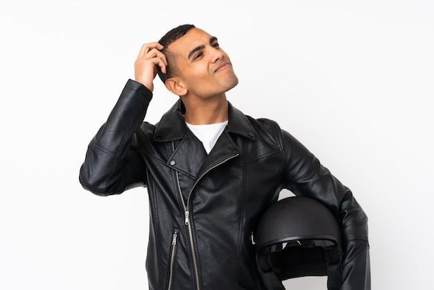 Молодой красивый человек с мотоциклетным шлемом над изолированной белой стеной, имеющей сомнения и с выражением лица путать