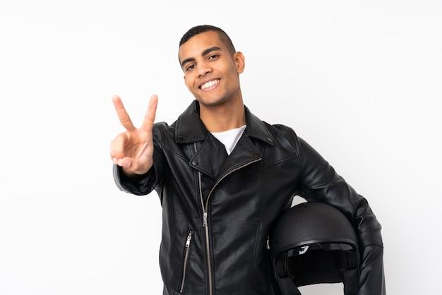 笑顔と勝利のサインを示す分離の白い壁の上のオートバイのヘルメットを持つ若いハンサムな男