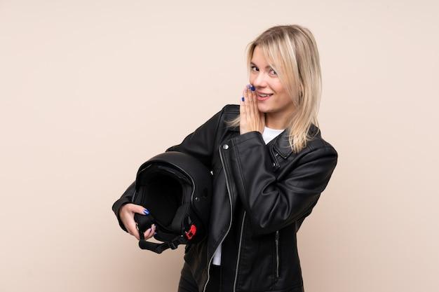 何かをささやく孤立した壁の上のオートバイのヘルメットを持つ若いブロンドの女性