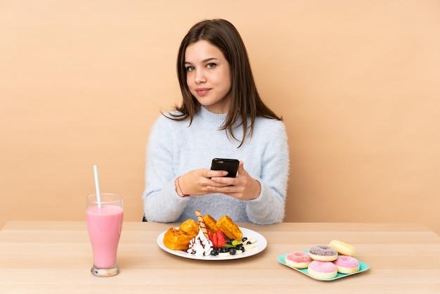 Девочка-подросток ест вафли, изолированные на бежевой стене, отправив сообщение с мобильного телефона
