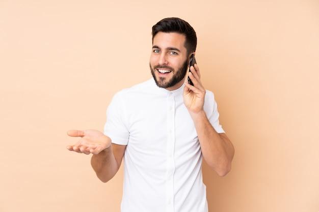 誰かと携帯電話との会話を維持するベージュの壁に分離された白人のハンサムな男
