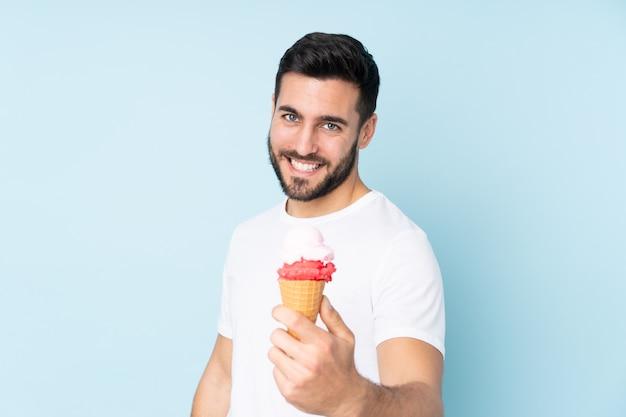 Кавказский мужчина с корнет мороженым, изолированных на синей стене с счастливым выражением