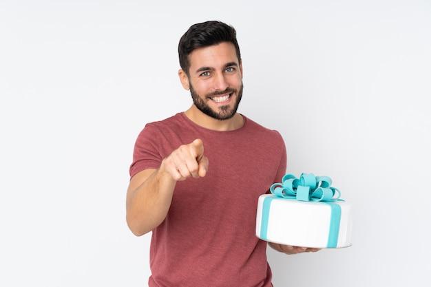 Шеф-кондитер с большим тортом, изолированным на белой стене, уверенно показывает на тебя пальцем