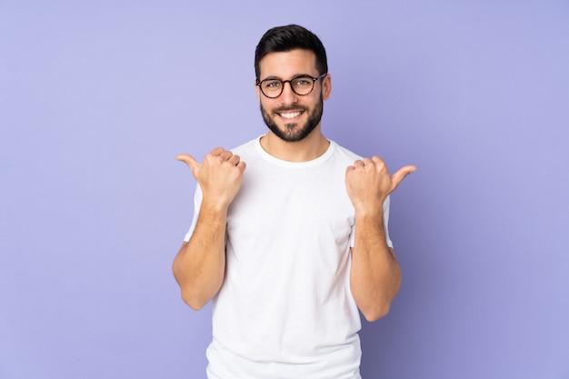 ジェスチャーと笑みを浮かべて親指で隔離された壁の上の白人のハンサムな男