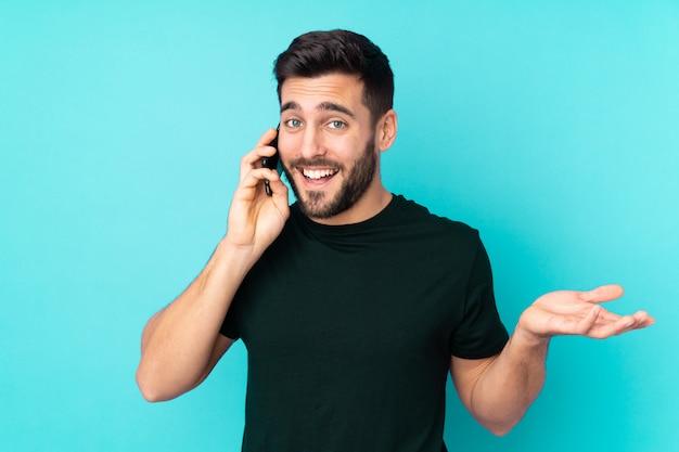 誰かと携帯電話との会話を維持する青い壁に分離された白人のハンサムな男