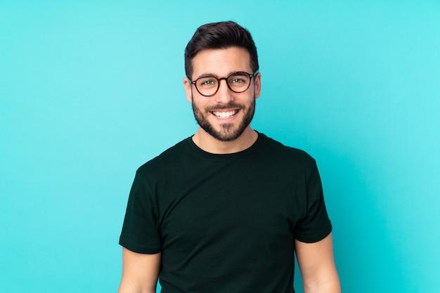 メガネと幸せの青い壁に分離された白人のハンサムな男