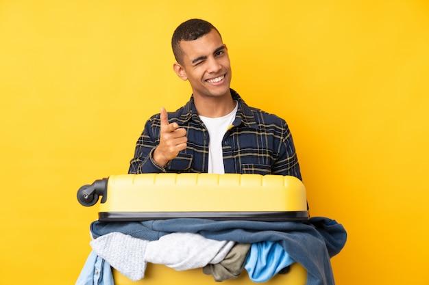 Путешественник с чемоданом, полным одежды, над желтой стеной показывает пальцем на тебя