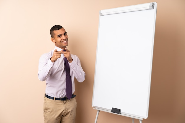 Молодой деловой человек на изолированной стене, давая представление на белой доске и указывает пальцем на вас