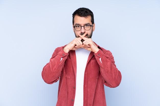 沈黙のジェスチャーの兆候を示す青い壁にコーデュロイのジャケットを着ている若い白人男