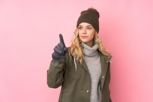 透明なスクリーンに触れるピンクの壁に分離された冬の帽子を持つ若い女性