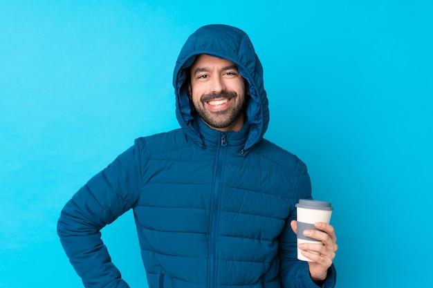 Укомплектуйте личным составом нося зимнюю куртку и держащ кофе на вынос над изолированной голубой стеной представляя с оружиями на бедре и усмехаться