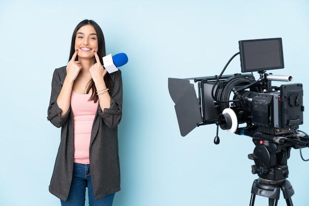 マイクを保持し、幸せで楽しい表情で笑顔の青い壁に分離されたニュースを報告するレポーター女性