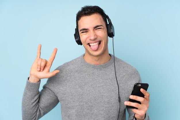 Молодой красавец, изолированные на синей стене прослушивания музыки с мобильного телефона, делая рок жест
