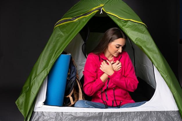 心の痛みを持っているキャンプの緑のテントの中の若い女性