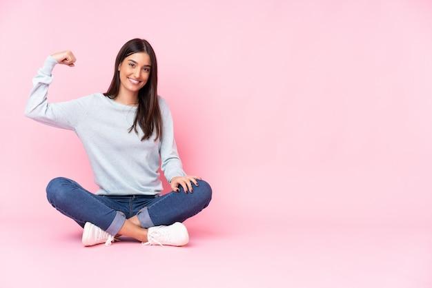 Молодая женщина на розовой стене делает сильный жест