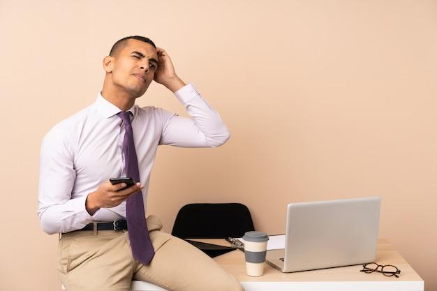 Молодой деловой человек в офисе, имея сомнения и с выражением лица путать