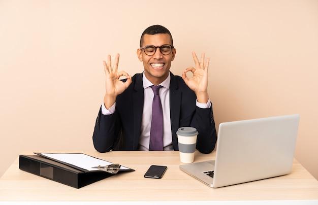 Молодой деловой человек в своем офисе с ноутбуком и другими документами в позе дзен
