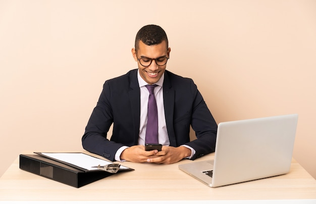 Молодой деловой человек в своем офисе с ноутбуком и другие документы, отправив сообщение с мобильного телефона