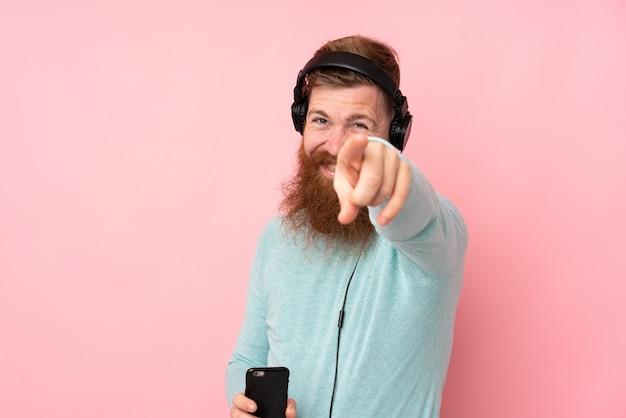 Рыжий мужчина с длинной бородой на изолированной розовой стене, слушая музыку и указывая на фронт