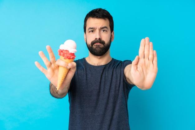 Молодой человек с мороженым корнет над синей стеной делает жест остановки и разочарован