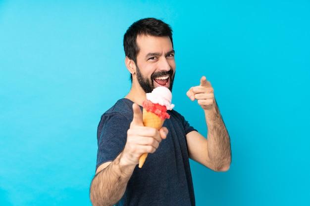 Молодой человек с мороженым корнет над синей стеной указывает пальцем на вас во время улыбки