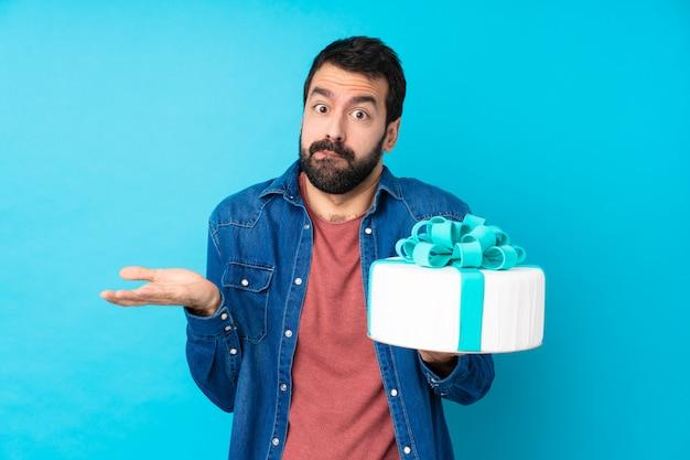 Молодой красавец с большой торт над синей стеной, возникли сомнения при поднятии руки