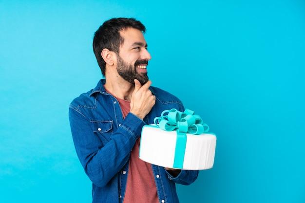 Молодой красавец с большой торт над синей стеной, глядя в сторону
