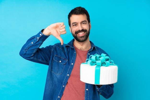 Молодой красавец с большой торт над синей стеной, показывая большой палец вниз