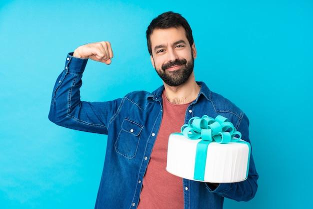 Молодой красавец с большой торт над синей стеной делает сильный жест
