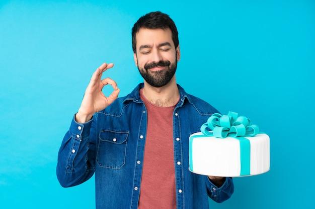 Молодой красавец с большой торт над синей стеной в позе дзен
