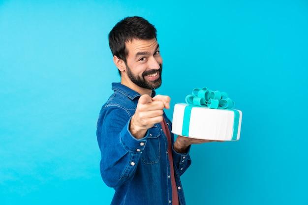 Молодой красавец с большой торт над синей стеной показывает пальцем на вас, улыбаясь