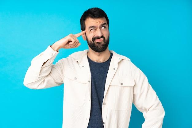 頭に指を置く狂気のジェスチャーを作る分離の青い壁に白いコーデュロイジャケットを持つ若いハンサムな男