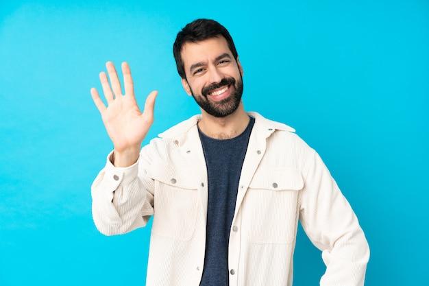 幸せな表情で手で敬礼分離の青い壁に白いコーデュロイジャケットと若いハンサムな男