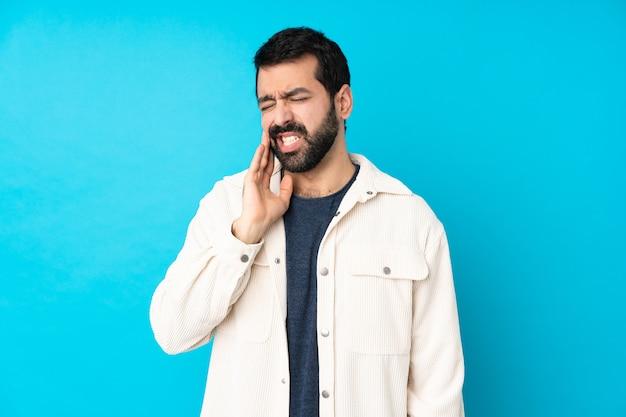 歯痛で孤立した青い壁に白いコーデュロイジャケットを持つ若いハンサムな男