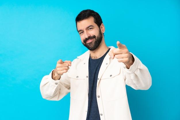 Молодой красавец с белой вельветовой курткой на синей стене указывает пальцем на вас во время улыбки