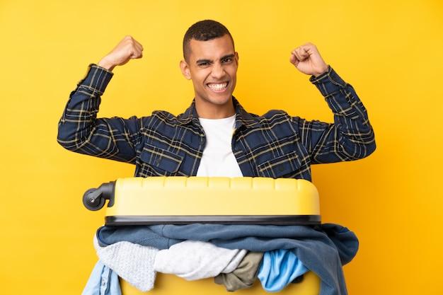 Человек путешественника с чемоданом, полным одежды над изолированной желтой стеной, празднует победу